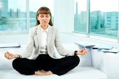 Portrait of attractive office worker meditating in office Stock Photos