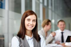 a beautiful businesswoman looking at camera with working partners behind - stock photo