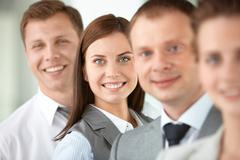 portrait of friendly leader looking at camera between employees - stock photo