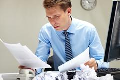 portrait of smart businessman looking through papers at workplace - stock photo