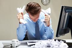 Portrait of stressed businessman with crumbled papers in hands at workplace Stock Photos