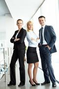 Portrait of friendly three business people looking at camera Stock Photos