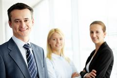 portrait of friendly leader looking at camera with two employees behind - stock photo
