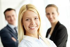 Portrait of friendly leader looking at camera with two employees behind Stock Photos
