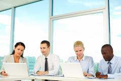 row of business people sitting in office and planning work - stock photo