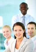 a beautiful businesswoman looking at camera with partners on background - stock photo
