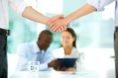 photo of handshake of business partners after striking deal on background of wor - stock photo