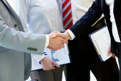 Hands of business partners handshaking after making agreement on background of t Stock Photos