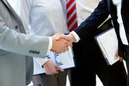 Stock Photo of hands of business partners handshaking after making agreement on background of t