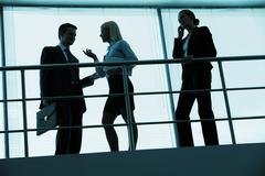 three outlines of business partners interacting in office - stock photo