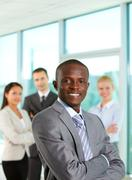 successful businessman looking at camera with his colleagues on background - stock photo