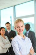Happy businesswoman looking at camera on backround of three partners Stock Photos