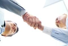 Below angle of successful associates handshaking after striking deal Stock Photos