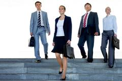 Portrait of confident business partners walking down stairs outdoors Stock Photos