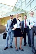 group of confident employees with documents looking aside outdoors - stock photo