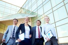 group of confident associates posing before camera outdoors - stock photo