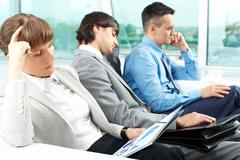 Portrait of serious woman thinking over paper with relaxing employees on backgro Stock Photos