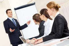 photo of successful businessman sharing ideas by whiteboard with partners at pre - stock photo