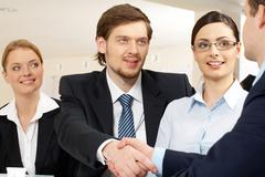 Photo of successful business partners handshaking after striking deal with prett Stock Photos