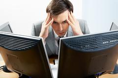 Image of businessman touching his head while looking at monitor with tired expre Stock Photos
