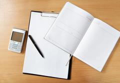 Image of workplace with paper, notepad, pen and palmtop gadget on it Stock Photos