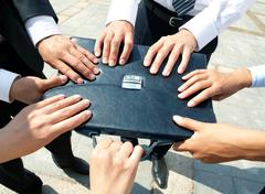 close-up of people hands holding black leather briefcase simultaneously - stock photo