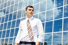 portrait of confident businessman on background of office building - stock photo