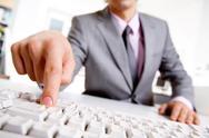 Image of businessman's finger pressing computer key Stock Photos