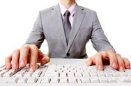 Stock Photo of close-up of businessman sitting at the table and typing