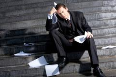 portrait of sad businessman sitting on stairs with papers in hands and lost expr - stock photo