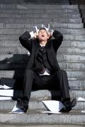 Despaired businessman screaming with papers in hands while sitting on staircase Stock Photos