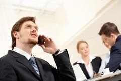 Portrait of confident businessman talking by cellphone with working team on back Stock Photos