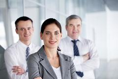 A business team with pretty leader in front looking at camera and smiling Stock Photos