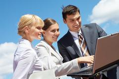photo of successful business partners looking at laptop during work - stock photo