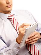 Close-up of male writing something in notepad over white background Stock Photos