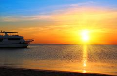 ship at anchor and sunrise over sea - stock photo
