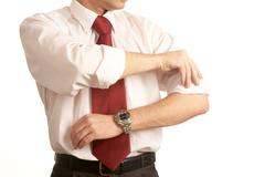close-up of male rolling up sleeves - stock photo