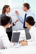 Photo of successful business partners looking at whiteboard during seminar Stock Photos