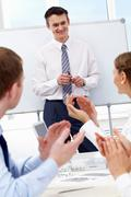 photo of successful businessman standing by whiteboard while his partners applau - stock photo