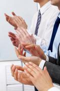 Kuva liikekumppaneiden kädet taputtaa klo kokouksessa Kuvituskuvat