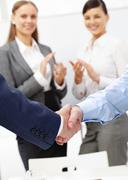 photo of handshake of business partners after striking deal on background of two - stock photo