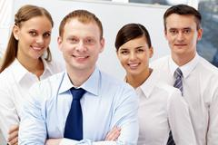 Stock Photo of portrait of friendly leader looking at camera with three employees behind