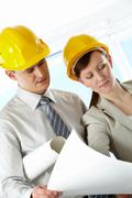 Portrait of two architects in helmets discussing document at meeting Stock Photos