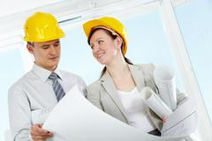 portrait of two architects in helmets holding blueprint - stock photo