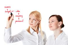 Two businesswomen drawing success scheme Stock Photos