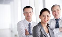 Stock Photo of a business team with pretty leader in front looking at camera and smiling