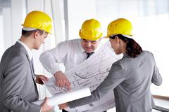 Three architects looking at a project and discussing it Stock Photos