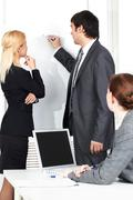 A business man drawing a plan on a whiteboard for his colleague Stock Photos