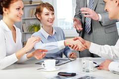 Image of business partners making an agreement with woman clapping her hands nea Stock Photos