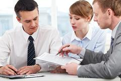 Photo of confident employees discussing papers at meeting Stock Photos